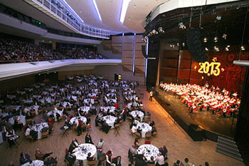 the orchestra performing on the stge, guests having dinner at round white clothed tables
