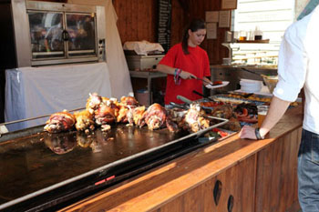 roasted pork knuckle and other meat dishes at one f the wooden stalls