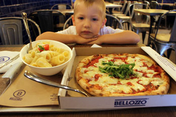 our 5-year old son with a round pizza and a bowl of pasta in Bellozzo