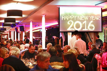 people on the Europa ship having dinner, Happy New 2016 displayed on a monitor