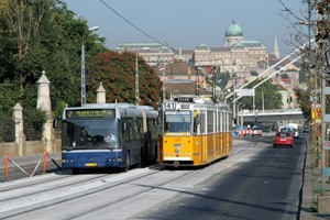 a yellow tram and a blue bus in Budapest