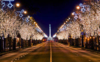 trees lining Andrassy ave, with festive lighting at night, the column at Heroes sqr. in the distance