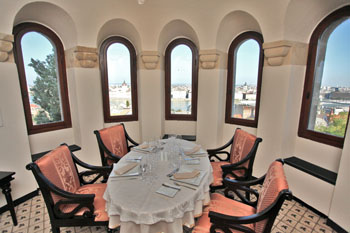 an elegantly set oval table with four pink chair, 3 vaulted windows with view of Pest
