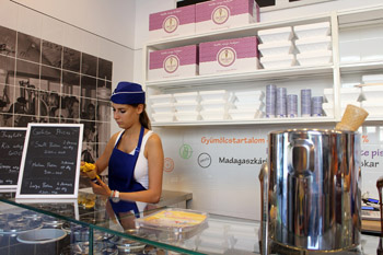 shop assistant in blue hat protioning ice cream in a cone