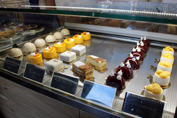 a selection of cakes behind a glass counter in Hiszteria Cremeria
