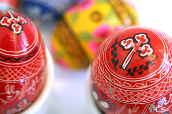 2 red and a yellow easter egg with folk motifs painted on them