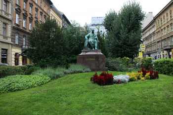 statue of Mor Jokai surrounded by flowers and green lawn