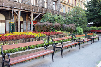 three wooden benches with flower beds in the background