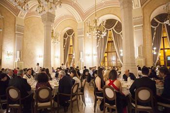 people having festive NYE dinner in an elegant arcaded dining hall