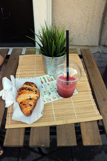 a croissant and strawberry smoothie in a plastic cup with a straw on a small wooden table