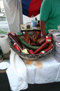 Hungarian paprika salami and sausages with a green cucumber in a woven basket