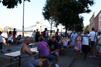 people sitting on benches placed on the street in Buda near Chain Bridge