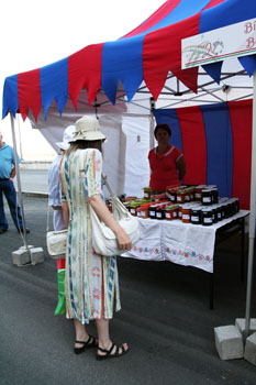 two ladies in hat at a stall selling jams and preserves