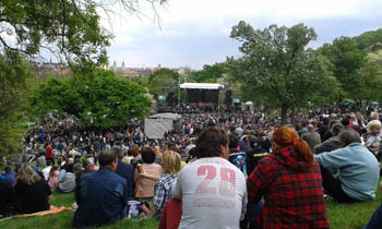 people sitting on the grass at a concert in Taban