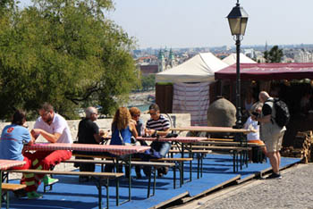 people sitting on wooden benches , eating and sipping wine