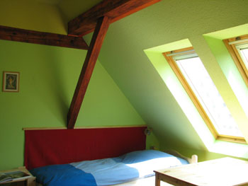 an attic room in 7x24 hostel with lime green walls
