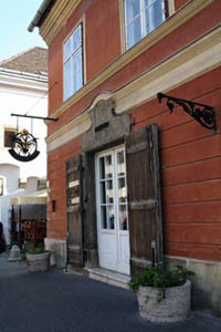the red facade and wooden doors at the entrance of the pharmacy musuem