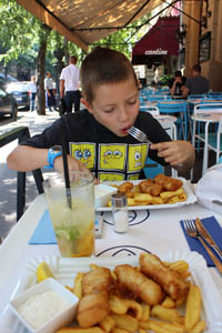 our 10-year old boy eating fish and chips on the terrace