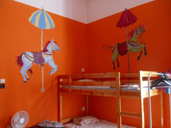 a cheery bedroom in Big Fish Hostel with orange walls