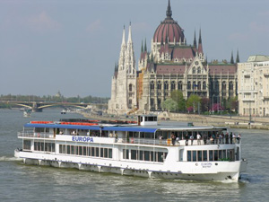 a double decker cruise boat on the Danube at the Parliament
