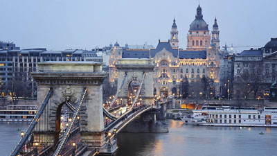 panoramic view of the Chain bridge , a white ship, the Gresham Palace and the Basilica at dusk