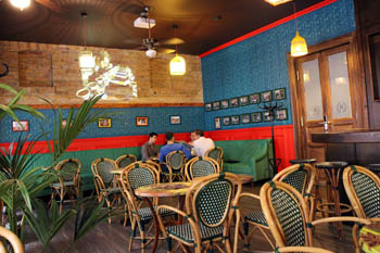 the blue-green interior of the cafe with reed chairs