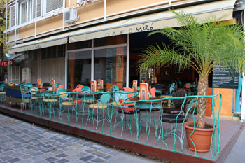 green metal chairs and tables on the terrace of Cafe Miró
