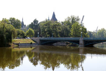 part of the greenish colored lake and a bridge, the tower of Vajdahunyad in the background