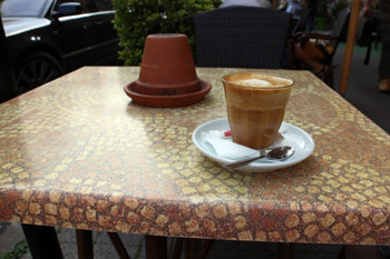 a flat white in a glass on a terra cotta table at Coytote cafe's terrace