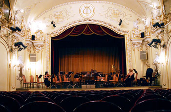 an orchestra playing on the stage of the Danube Palace's concert hall