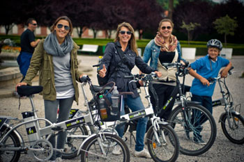 3 young ladies standing next to their e-bikes