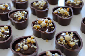 heart-shaped bonbons with ganache filling and nut sprinkles
