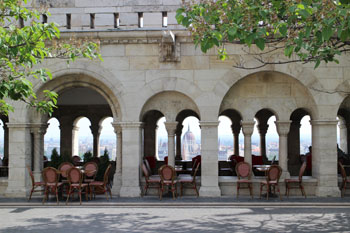 tables and chairs on the first level terrace of Halaszbasty Resturant, the view of Paliament in the background