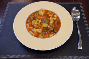 goulash served in a round plate placed on a dark brown place mat