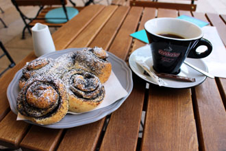 chocolate snails on a palte and coffee in a black cup on a wood terrace table