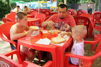 my husband, our 2 sons, and me eating langos at a red plastic table on Palatinus