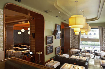 tables with retro cloth, large yellow lamps from the ceiling and a window overlooking the street