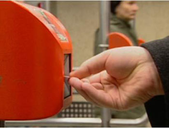 a hand inserting a ticket into an orange ticket validation machine