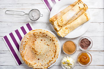 flat and rolled up pancakes on separate round plates, jam, cocoa powder, cinnamon in small glass bowls