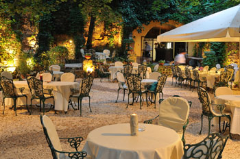 small round tables with 4 chairs in the garden of Pavillon de Paris at night