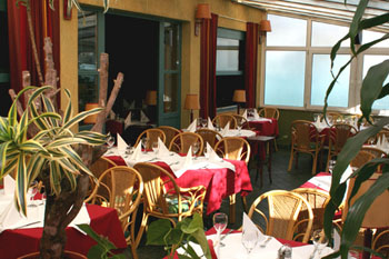 the terrace of Remiz cafe with round red-clothed tables and some potted plants