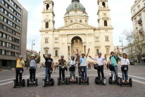 a group of Segway riders in front of the Basilica in summer