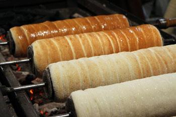 four rolls of Sekler cake baking over coal