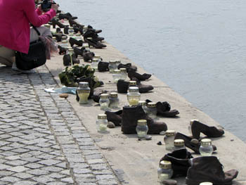 """a woman in a pink jacket is taking photos of the """"shoe"""" memorial"""