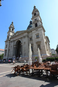 front view of the basilica and part of a cafe terrace on the square