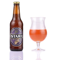 half a glass of Stari pum beer with the bottle to the left