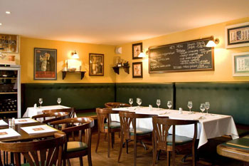 interior of Stelazsi with white clothed tables and black board with the menu on the yellow wall