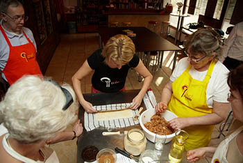 a young woman rolling up strudel dough 3-4 other students watching her
