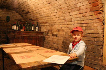 our 5-year old son in a red baseball cap sitting at a table in a cellar