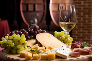 a half glass of white with bunches of grape and chunks of cheese on a wooden table